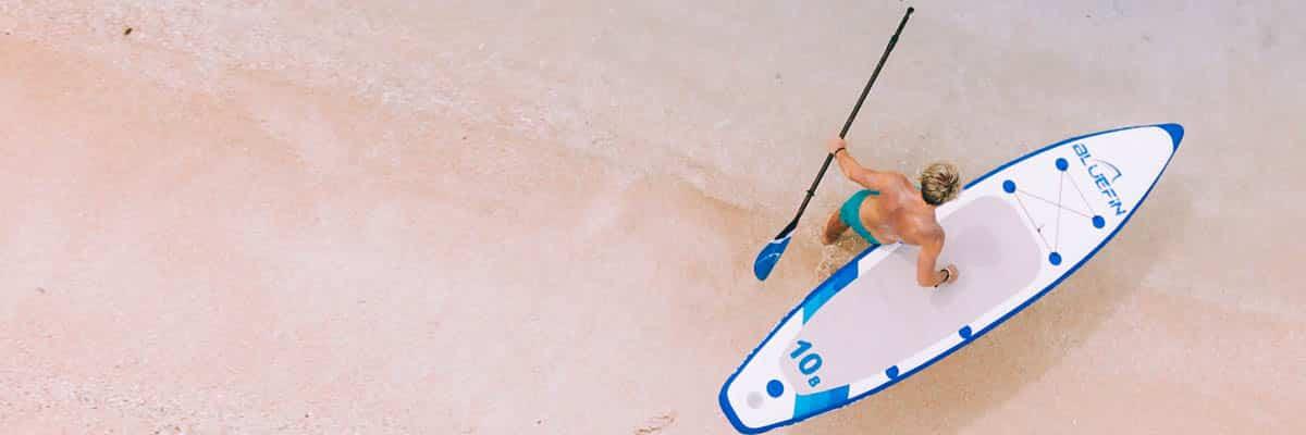 mann mit bluefin sup board in seichtem wasser