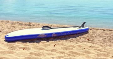 SUP Board am Strand mit SUP Finnen, die nach oben zeigen.