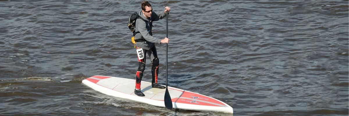 mann paddelt auf sup board mit schuhen an