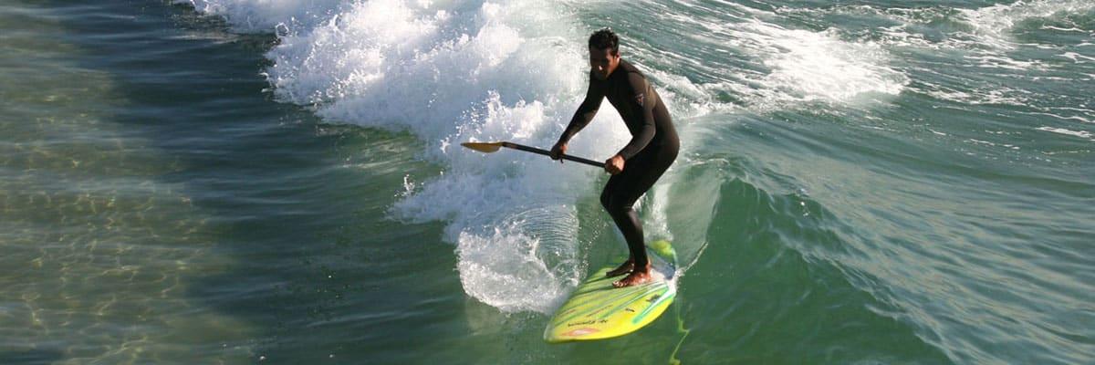mann surft mit sup board auf welle mit guter wave sup technik