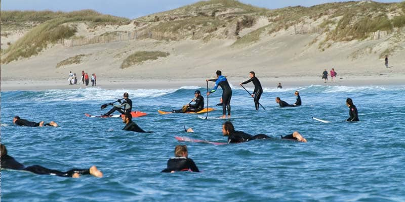 wave sup surfer und andere surfer warten auf die richtige Welle
