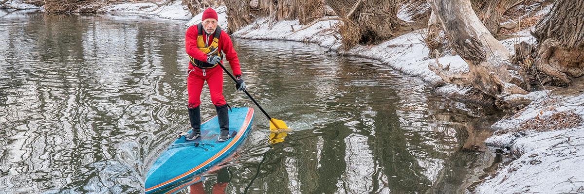 Mann macht einen SUP Trockenanzug Test im Winter.